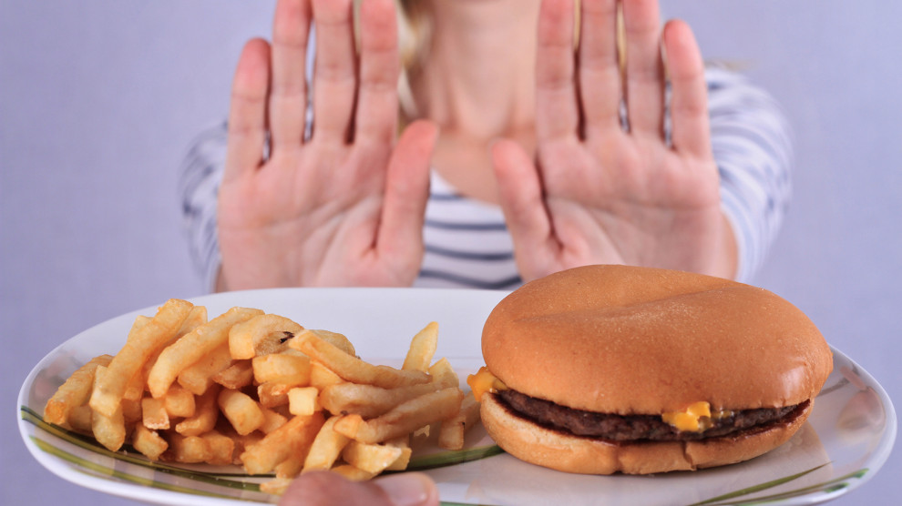 Woman refuses to eat junk food .